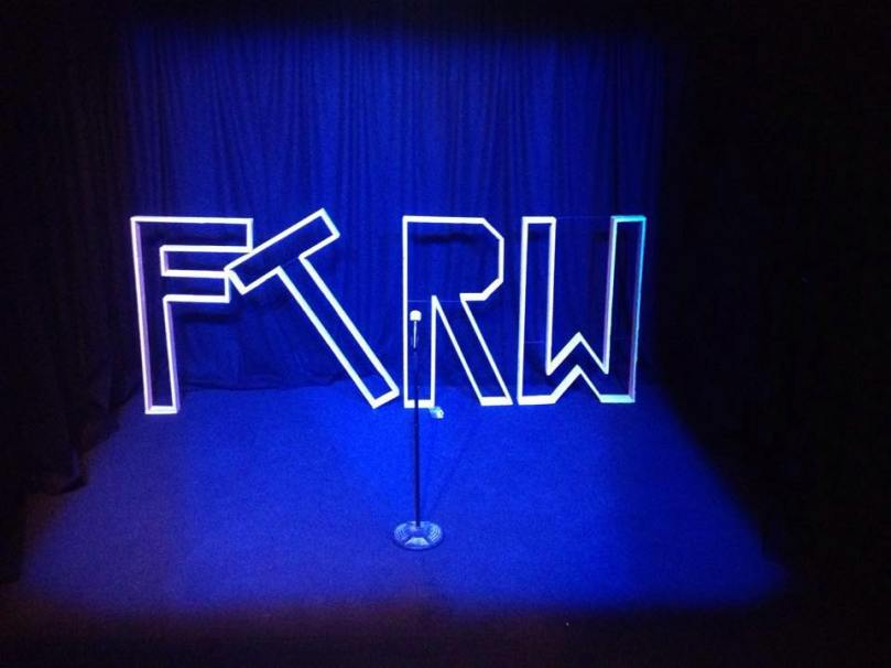 "Upstairs at the Western stage and curtains under a blue light. A microphone stand in the middle. Behind the mic, large wood versions of the letters ""F"" ""T"" ""R"" and ""W"" for ""Find the Right Words"" stand one next to the other, the ""T"" resting diagonally on the ""F""."
