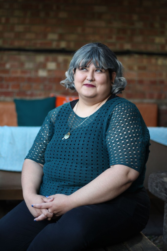 Picture of Cynthia, a fat nonbinary latinx person, sitting on a bench in a patio. They are wearing black trousers, a black vest and a see-through dark green top with holes pattern. They are also wearing a necklace, green nails, a septum piercing, red wine coloured lips, and a silver bob wig. Hands together, fingers laced, resting between their legs. Cynthia is looking afar, thinking about thoes taquitoes. There is a large corner bench on the background, with orange and green cushions, on a red brick wall.